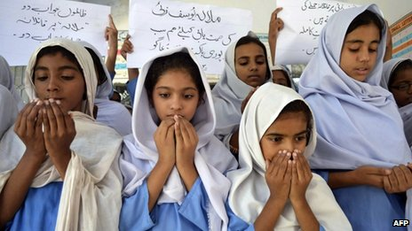 Pakistani schoolgirls in headscarves  pray