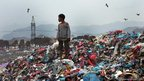 A child stands on rubbish at the al-Maklaab landfill on the outskirts of Taiz