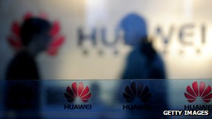 Staff and visitors walk pass the lobby at the Huawei office in Wuhan, central China