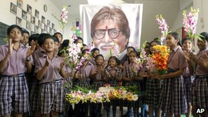 Indian schoolchildren stand in front of a portrait of Bollywood&quot;s biggest star Amitabh Bachchan, at an event a day ahead of his 70th birthday, in Mirzapur, India, Wednesday, Oct. 10, 2012