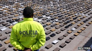 A narcotics police officer stands next to bundles of cocaine in Riohacha, Guajira department