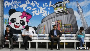 People rest on a bench in front of an advertisement of an electronics shop in Tokyo, 27 Sept 2012