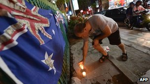 A tourist lights a candle at the Sari Club blast site on 10 October 2012