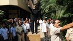 Bollywood star Amitabh Bachchan greets fans gathered outside his residence
