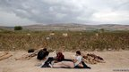 Syrian men rest after crossing to Turkey 