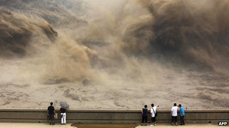 Visitors gathering to giant gushes of water released from the Xiaolangdi dam to clear up the sediment-laden Yellow river and to prevent localized flooding