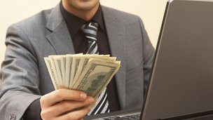 Man holds cash whilst looking at laptop
