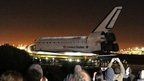 Spectators watch from the airport perimeter as the Space Shuttle Endeavour begins its final journey at Los Angeles International Airport (LAX) to its permanent home, in the early morning hours October 12, 2012 in Los Angeles, California.