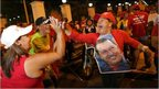 Supporters of Venezuela's President Hugo Chavez cheer after polling stations closed