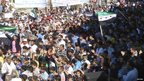 Demonstrators hold opposition flags during a protest against Syrian President Bashar al-Assad after Friday prayers in Houla, near Homs. (12 October 2012.) Image provided to Reuters by Shaam News Network.