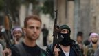Syrian opposition fighters walk in the northern Syrian city of Aleppo (11 October 2012).