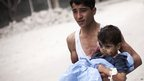 A Syrian youth holds a child injured by shelling near Dar al-Shifa hospital in Aleppo (11 October 2012).