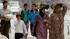 Syrians carry bread as they walk in the streets of the northern city of Aleppo (11 October 2012)