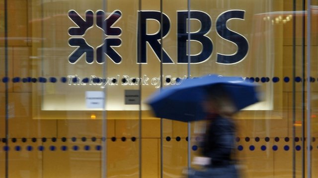 Woman with umbrella walking past the London headquarters of RBS