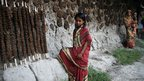 Girl wearing red sari standing next to wall with cow dung patties stuck to the wall