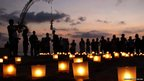 People gather around lit-up candles at Kuta Beach, Bali