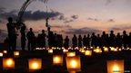 People gather around lit-up candles at Kuta Beach, Bali