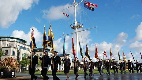 Canadian flag flies on Guernsey memorial mast as parade of standards walk past