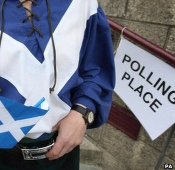 Man dressed in saltire flag outside polling booth