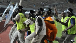 Riot police escort Ivorian players out of the stadium