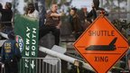 People gather near a shuttle crossing sign and a freeway sign that was taken down to make room as the space shuttle Endeavour is transported across Los Angeles (12/10/12)