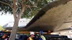 Crewmen wait as a tree blocks wing of Endeavour in Los Angeles, 13 October