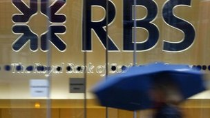 Women with umbrella walking passed RBS sign