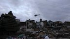Brazilian naval soldier in an armoured vehicle patrols the Manguinhos slum as a police helicopter flies above during a peacekeeping operation in Rio de Janeiro October 14, 2012.