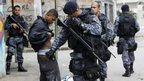 Police officers check a man during an operation to install a Pacifying Police Unit at Jacarezinho slum in Rio de Janeiro, Brazil, Sunday Oct. 14, 2012