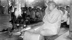 Prince Norodom Sihanouk, prays 3 August 1955 with Buddhist monks at 'Big Buddha' monastery in Siem Reap after he abdicated in favour of his father, Norodom Suramarit