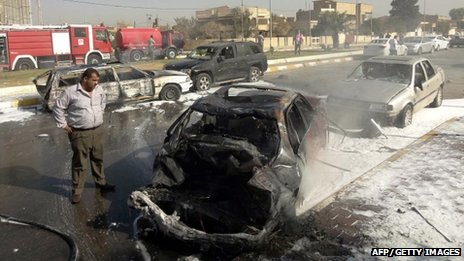 A man looks at destroyed vehicles after two car bombs exploded near the provincial government headquarters in Kirkuk, northern Iraq, on 15 October 2012.