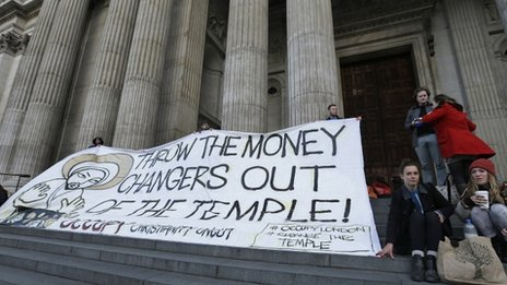 "Activists of the Occupy hold a banner saying ""Throw the Money Makers out of the Temple"" outside of St Paul's Cathedral in London"