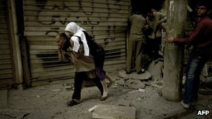 A man carries a woman from her destroyed home in the Shaar neighbourhood of the northern city of Aleppo, 13 October 2012.