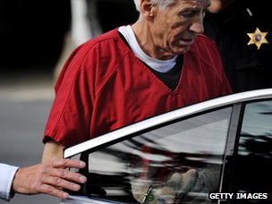 Former Penn State assistant football coach Jerry Sandusky is put in a car the Centre County Courthouse after being sentenced in his child sex abuse case