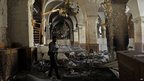 A Syrian rebel stands inside the damaged Umayyad Mosque