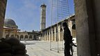 A Syrian rebel stands in the courtyard of the Umayyad Mosque