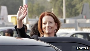 Australian Prime Minister Julia Gillard waves before getting into a car upon her arrival at the airport in New Delhi October 15, 2012.