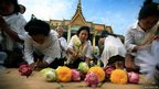 Women lay flower offerings and chant prayers at the Royal Palace in Phnom Penh, Cambodia