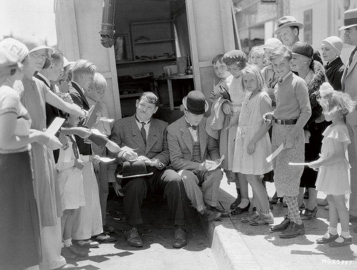 Stan Laurel and Oliver Hardy signing autographs for young fans on the set of their second feature film, Pack Up Your Troubles, MGM, 1932