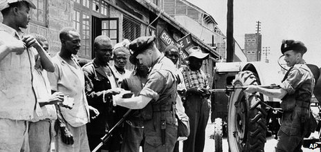British soldiers check the identity of men during a raid on parts of Nairobi, Kenya, on 5 October 1953, looking for Mau Mau members