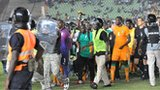 Police escort Ivory Coast players off the pitch in Dakar