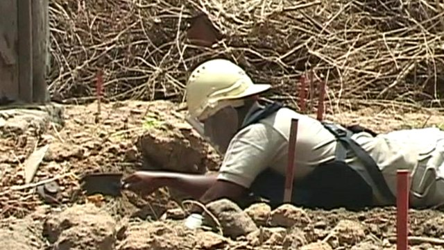 Woman digs around a landmine