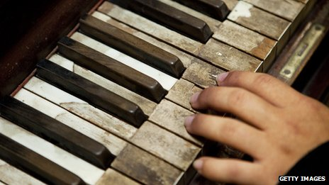 A woman's hands at the keyboard of an old piano