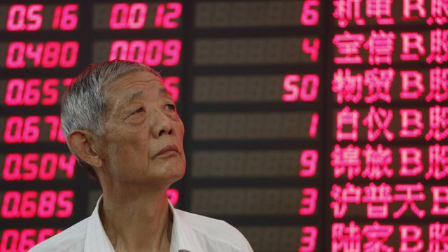 An investor looks at a stock price monitor in Shanghai