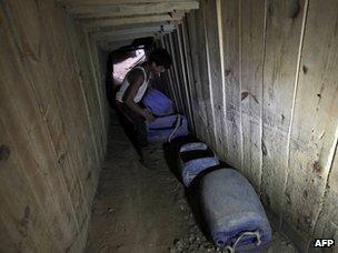 A man smuggles goods under the Gaza-Egypt border (30 September 2012)