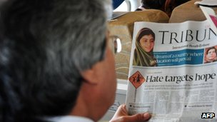 A man reads a newspaper report about Malala Yousufzai on a plane over Pakistan (10 Oct 2012)