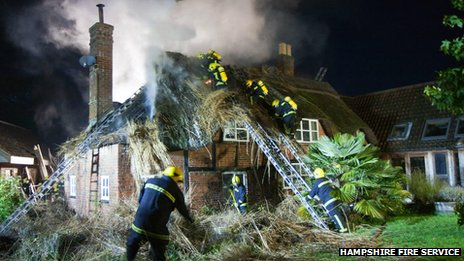 Firefighters tackle the blaze at the two-storey thatched house on Romsey Road in Cadnam