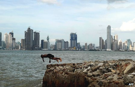 Boy is seen diving into the sea with the skyline of Panama City in the background