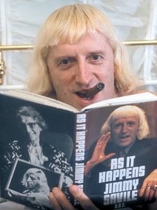 Jimmy Savile reading a copy of his autobiography
