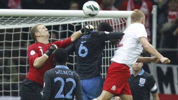 England keeper Joe Hart (left) misses punching out a corner and Kamil Glik (right) heads in for Poland